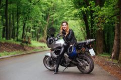 An attractive girl on a sports motorbike posing outside stock image