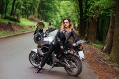 An attractive girl on a sports motorbike posing outside stock photo