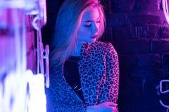 Sexy girl wear stylish leopard jacket standing near wall with purple neon light royalty free stock image