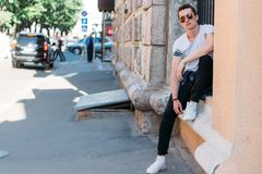 Attractive, sexy guy sits on the street in sunglasses. self-confidence, flatulence and arrogance. model, posing, portrait of a. Attractive, sexy guy sits leaning stock image