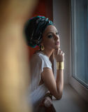 Attractive sexy lady in white blouse posing in window frame looking outside. Portrait of sensual young woman with turban Royalty Free Stock Photos