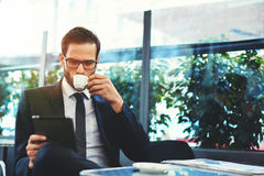 Attractive man in glasses drinking tea and browsing News. Portrait of handsome successful man drink coffee and look to the digital tablet screen sitting in stock photo