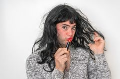 Attractive man wearing makeup looks like as a woman stock photo