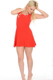 Attractive Sexy Playful Young Blonde Woman Wearing a Short Red Mini Dress. Attractive Sexy playful Young Blonde Haired Woman in Her Twenties Wearing a Short Red Stock Photo