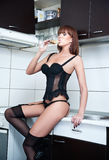 Attractive sexy red hair female with black lingerie and stockings drinking wine in a modern kitchen. Portrait of sensual redhead Royalty Free Stock Image