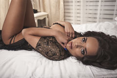 Attractive and sexy seductive young woman with dark and perfect body wearing black lingerie, on bed hiding boobs with hands Royalty Free Stock Photo