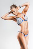 Attractive sexy sporty woman in blue and silver bikini. In studio Stock Image