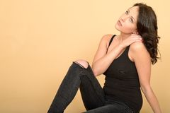 Attractive Sexy Thoughtful Young Woman Wearing Black Jeans and Vest Top Stock Images