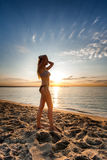 Attractive sexy woman in bikini walking on sand on lonely beach. On sunrise sunset Royalty Free Stock Image