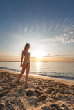Attractive sexy woman in bikini walking on sand on lonely beach. On sunrise sunset Stock Photos