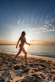 Attractive sexy woman in bikini walking on sand on lonely beach. On sunrise sunset Stock Photography