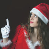 Attractive woman dressed Santa hat pointing at copy space Stock Photo