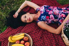 Attractive woman lay on red fabric on grass during picnic. Vacation concept