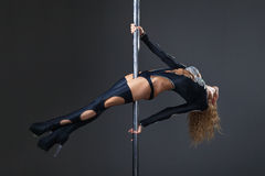 Attractive sexy woman pole dancer performing Royalty Free Stock Photography