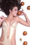Attractive sexy woman with shine gold bikini lying, Christmas balls around her Royalty Free Stock Photos