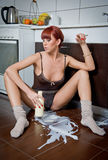 Attractive sexy woman sitting on the kitchen floor spilling milk from a bottle Royalty Free Stock Photography