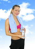 Attractive and sexy woman in sport clothes with towel drinking water bottle at gym workout Royalty Free Stock Photography