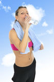 Attractive and sexy woman in sport clothes with towel drinking water bottle at gym workout Stock Images