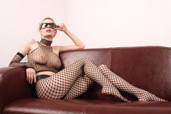 Attractive sexy woman in sunglasses sitting on sofa Royalty Free Stock Photo