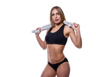 Attractive sexy woman after workout with towel isolated over white background. Young female with muscular body. Stock Photo