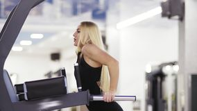 Attractive young blond girl doing pull ups at the gym. Healthy lifestyle. Endurance and motivation. Attractive young blond girl doing pull ups at the gym stock video