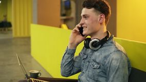 Attractive sexy young guy in demin shirt sitting in well lit indoors space talking to someone on the phone. Attractive sexy young guy in demin shirt sitting in stock video footage