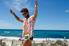 Attractive sexy young man in swimwear and sunglasses posing on the beach with arms raised on Corsica island, France. stock photography