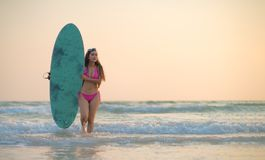 Attractive sexy young woman in red swimsuit is standing on beach with white surfboard in hands and smiling stock images