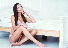 Attractive sexy young woman in underclothes sitting at bed Stock Image