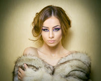 Attractive young woman wearing a fur coat posing provocatively indoor. Portrait of sensual female with creative haircut royalty free stock image