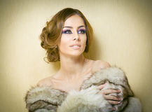Attractive sexy young woman wearing a fur coat posing provocatively indoor. Portrait of sensual female with creative haircut Royalty Free Stock Images