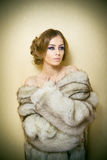 Attractive sexy young woman wearing a fur coat posing provocatively indoor. Portrait of sensual female with creative haircut Royalty Free Stock Image