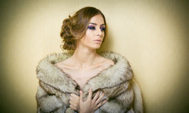 Attractive sexy young woman wearing a fur coat posing provocatively indoor. Portrait of sensual female with creative haircut Stock Photo