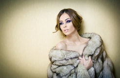 Attractive sexy young woman wearing a fur coat posing provocatively indoor. Portrait of sensual female with creative haircut Stock Photos