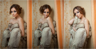 Attractive sexy young woman wearing a fur coat posing provocatively indoor. Portrait of sensual female with creative haircut Royalty Free Stock Photo