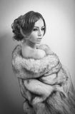 Attractive sexy young woman wearing a fur coat posing provocatively indoor. Portrait of sensual female with creative haircut Stock Photography