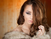 Attractive young woman wearing a fur coat posing provocatively indoor. Portrait of sensual female with creative makeup Royalty Free Stock Images