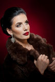 Attractive sexy young woman wearing a fur coat posing in studio on dark purple background. Portrait of sensual female Royalty Free Stock Image