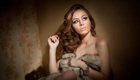 Attractive young woman wrapped in a fur coat sitting in hotel room. Portrait of sensual female daydreaming near a wall Royalty Free Stock Images