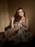 Attractive young woman wrapped in a fur coat sitting in hotel room. Portrait of sensual female daydreaming near a wall Stock Image