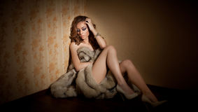 Attractive sexy young woman wrapped in a fur coat sitting in hotel room. Portrait of sensual sad female Royalty Free Stock Images