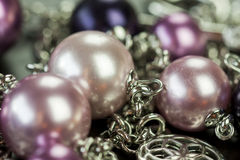 Attractive shiny purple beads on jewellery. Close up of three attractive shiny purple beads attached by silver chains on an item of jewellery in a fashion and Stock Image