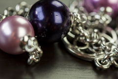 Attractive shiny purple beads on jewellery. Close up of three attractive shiny purple beads attached by silver chains on an item of jewellery in a fashion and Stock Photos