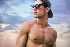 Handsome young man on beach with baseball cap royalty free stock photo