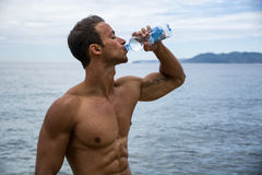 Attractive shirtless muscleman on the beach drinking water Royalty Free Stock Photos