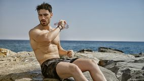 Attractive shirtless muscleman pouring water on his chest from plastic bottle stock images