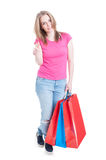 Attractive shopaholic girl showing thumb up or like gesture Stock Photography