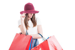 Attractive shopaholic holding her hat acting mysterious or hidin Stock Photos