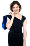 Attractive shopaholic woman carrying shopping bag. Cheerful young model beaming with happiness, bag slung over shoulder Royalty Free Stock Images