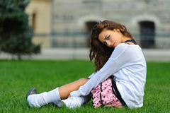 Short skirt attractive young girl sitting on the g Stock Photography